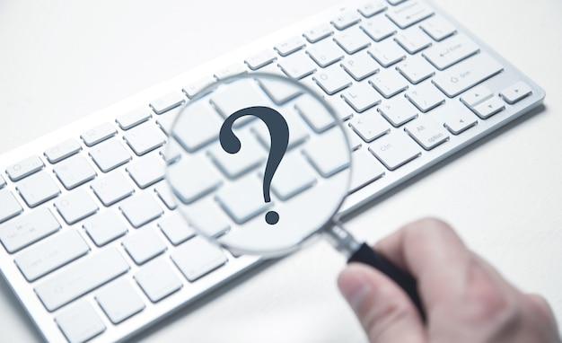 Męskiej dłoni trzyma lupę i znak zapytania na klawiaturze komputera.