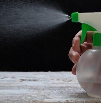 Męskiej dłoni wyciskanie spray z żelem alkoholowym na czarnym tle.