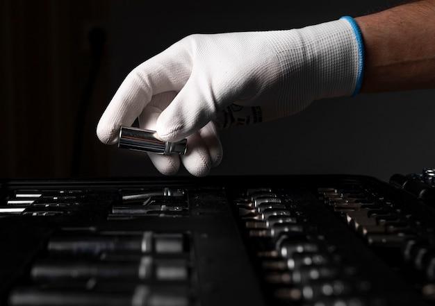 Męskiej dłoni z bliska w białej rękawiczce nad otwartym zestawem narzędzi z metalowych narzędzi do naprawy samochodu i domu, głowa.