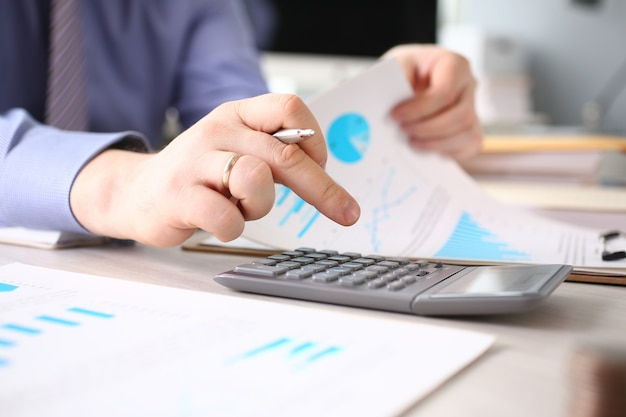 Męskiej dłoni za pomocą kalkulatora w miejscu pracy