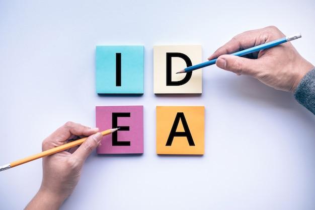 Męskiej i żeńskiej dłoni z ołówkiem i tekstem pomysłu na tle kolor papieru. biznesowa burza mózgów i koncepcje pomysłów kreatywności