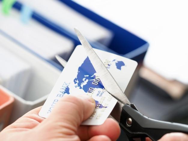Męskiej ręki bankowości tnąca karta z nożyce zbliżeniem