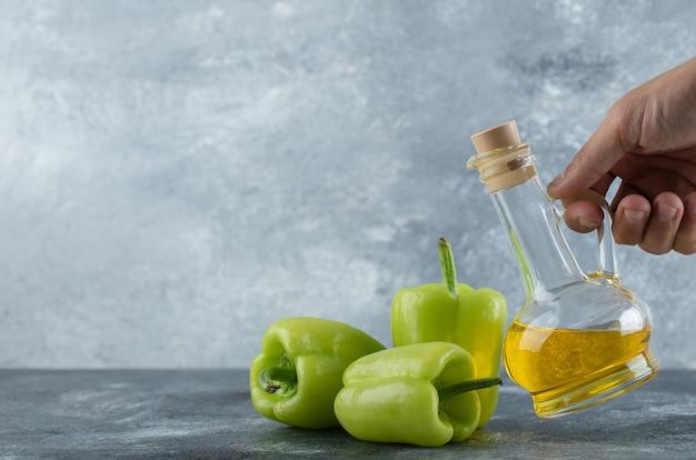 Męskiej ręki biorąc butelkę oleju ze stołu i świeżej papryki na stole.