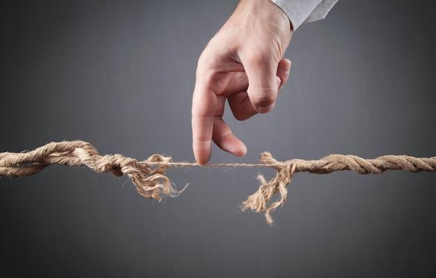 Męskiej ręki chodzenie postrzępione liny. ryzyko