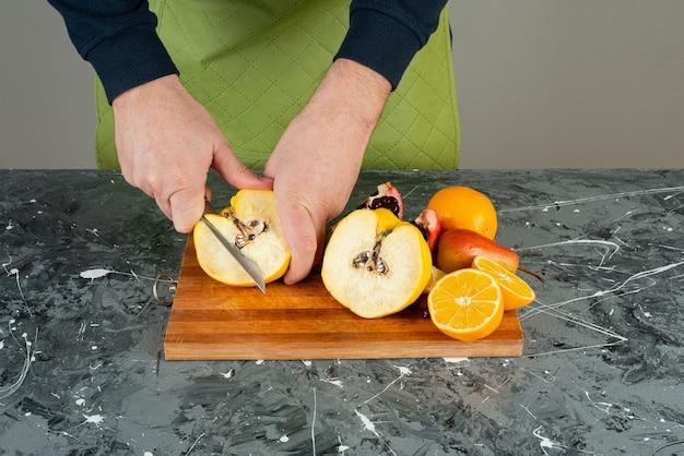 Męskiej ręki cięcia dojrzałej pigwy na drewnianej desce na stole.