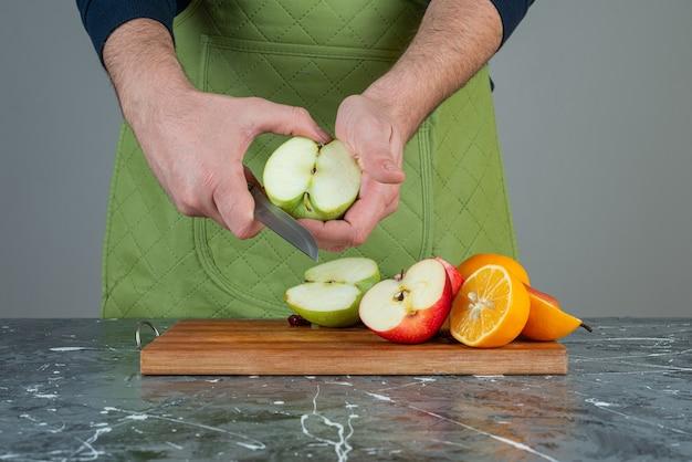 Męskiej ręki cięcia zielone jabłko na marmurowym stole.
