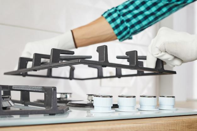 Męskiej ręki czy instalacja palnika na płycie gazowej w kuchni, z bliska. naprawa lub naprawa panelu sterowania gazem.