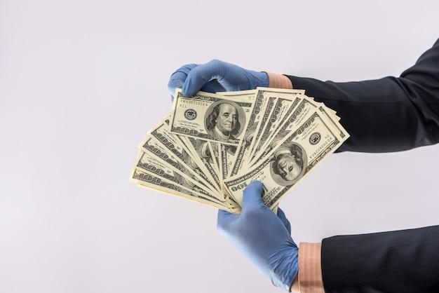 Męskiej ręki dać dolara zapłacić w rękawicach ochronnych dla bezpieczeństwa na białym tle. koncepcja medyczna covid 19 koronawirus