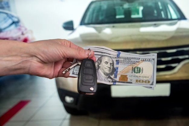 Męskiej ręki daje pieniądze i bierze kluczyki do samochodu, nowy samochód jako tło. finanse