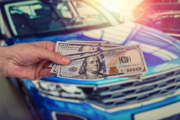 Męskiej ręki dolar, weź pieniądze na tle samochodu. pomysł na biznes