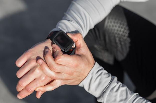Męskiej ręki dostosowując zegarek sportowy