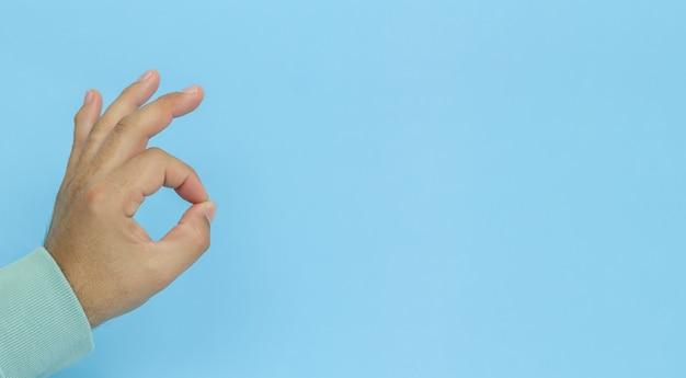 Męskiej ręki gestykuluje znak ok na niebieskim tle.