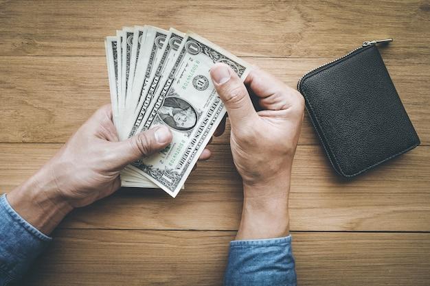 Męskiej ręki holing dolara pieniędzy z portfelem na stół z drewna