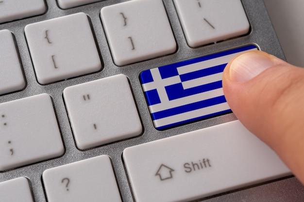Męskiej ręki naciskając przycisk klawiatury z flagą grecji na nim.