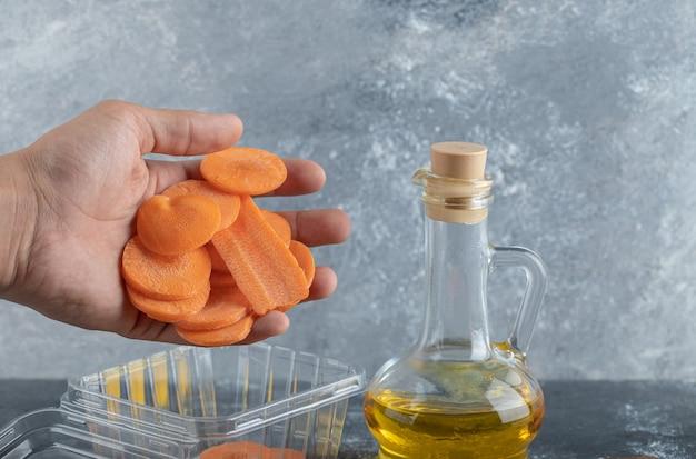 Męskiej ręki odlewania plastry marchwi w plastikowym pojemniku.