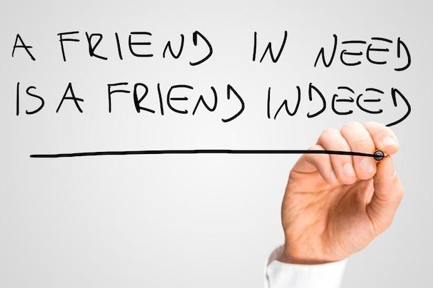 Męskiej ręki pisanie frazy przyjaciel w potrzebie jest rzeczywiście przyjacielem na wirtualnym ekranie.