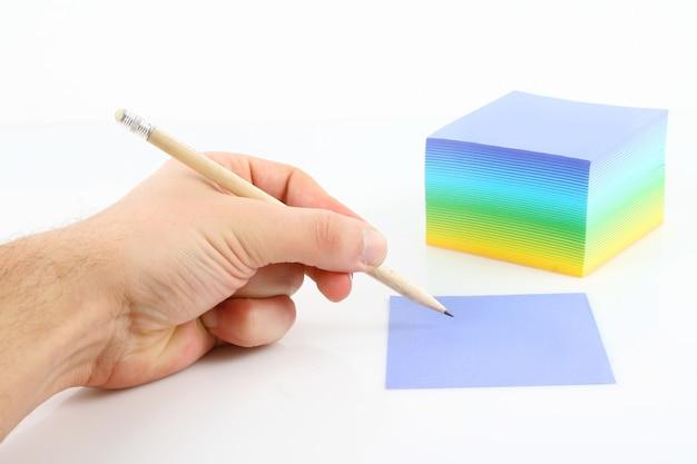 Męskiej ręki pisanie na kolorowym papierze na białym