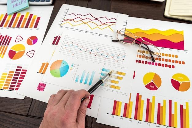 Męskiej ręki pokazano schemat lub wykres na sprawozdanie finansowe za pomocą pióra. wzrost i sukces