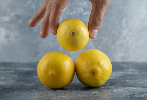 Męskiej ręki przy świeżej cytrynie ze stosu.