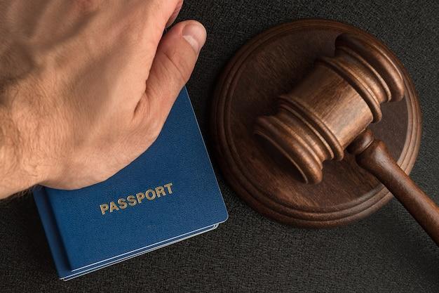 Męskiej ręki trzyma paszport obok drewniany młotek