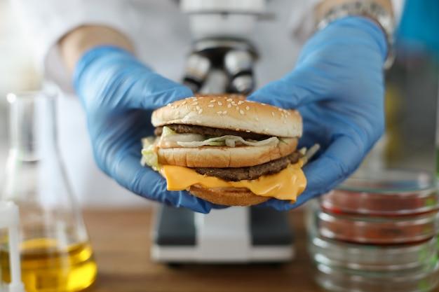 Męskiej ręki trzymaj burger w dłoni z niebieskimi rękawiczkami ochronnymi