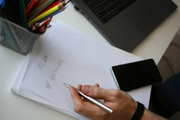 Męskiej ręki trzymaj srebrny długopis komponujący listę zadań