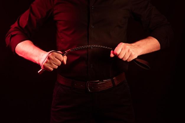 Męskiej ręki trzymającej czarny skórzany bicz.