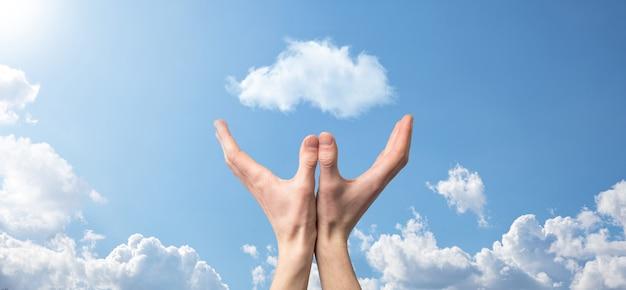 Męskiej ręki trzymającej dom ikona na niebieskim tle. koncepcja ubezpieczenia i bezpieczeństwa nieruchomości. koncepcja nieruchomości. warunki pogodowe, zachmurzenie. baner z miejscem na kopię