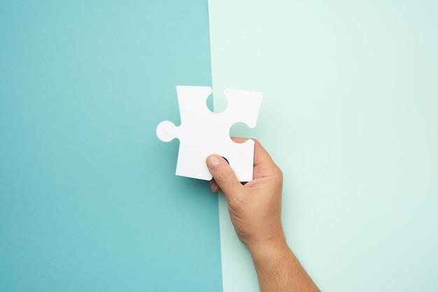 Męskiej ręki trzymającej duże białe papierowe puzzle puste, koncepcja biznesu