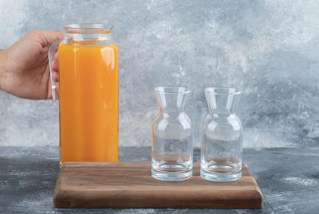 Męskiej ręki trzymającej dzbanek soku pomarańczowego.