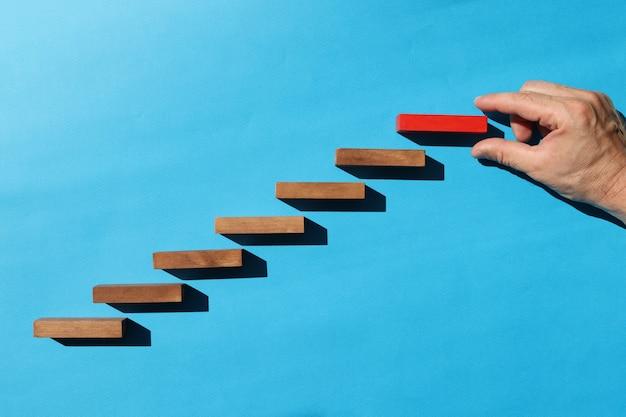 Męskiej ręki trzymającej górny czerwony drewniany klocek na niebieskim tle osiągnięcie celu rozwoju kariery
