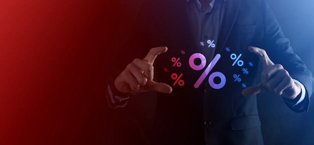 Męskiej ręki trzymającej ikona procent stopy procentowej na niebieskim tle. koncepcja stóp procentowych finansowych i hipotecznych. baner z miejsca na kopię.