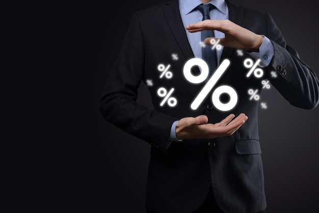 Męskiej ręki trzymającej ikona procent stopy procentowej na niebieskim tle. koncepcja stóp procentowych finansowych i hipotecznych. baner z miejscem na kopię
