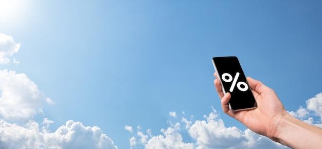 Męskiej ręki trzymającej ikona procent stopy procentowej na tle błękitnego nieba. koncepcja stóp procentowych finansowych i hipotecznych. baner z miejsca na kopię.