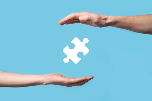 Męskiej ręki trzymającej ikona układanki na niebieskim tle. elementy reprezentujące połączenie dwóch firm lub joint venture, partnerstwo, koncepcję fuzji i przejęć.