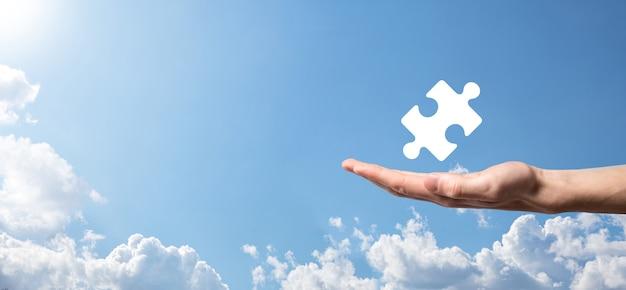 Męskiej ręki trzymającej ikona układanki na niebieskim tle. utwory reprezentujące połączenie dwóch spółek lub joint venture, spółkę, koncepcję fuzji i przejęć.