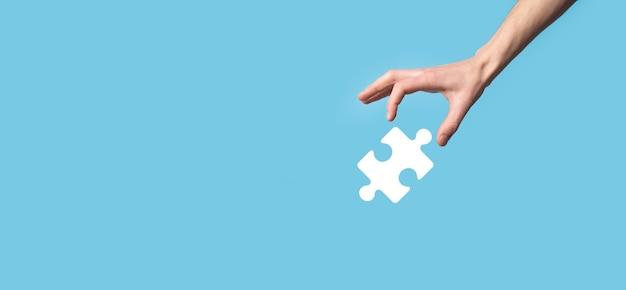 Męskiej ręki trzymającej ikona układanki na niebieskim tle