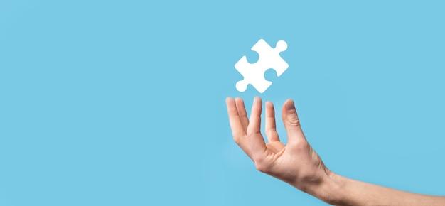 Męskiej ręki trzymającej ikona układanki na niebieskim tle.