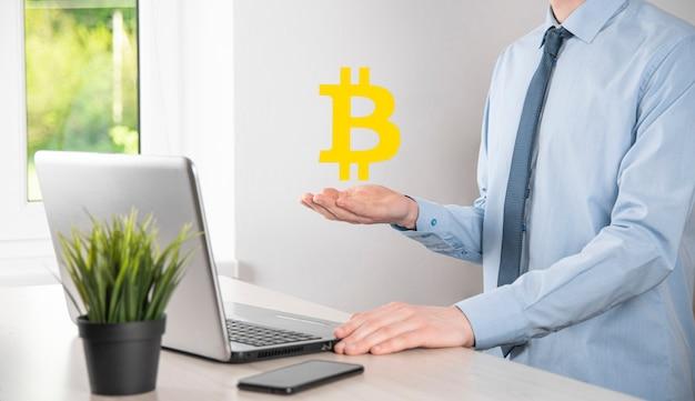 Męskiej ręki trzymającej ikonę bitcoin na niebieskim tle. bitcoin kryptowaluta cyfrowa moneta bitowa btc waluta technologia biznesowa koncepcja internetu.