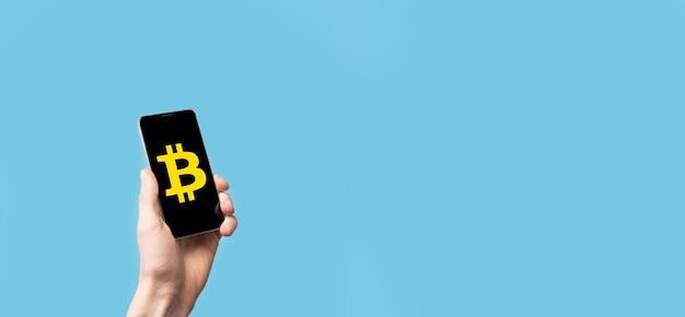 Męskiej ręki trzymającej ikonę bitcoin na niebieskim tle. bitcoin kryptowaluta cyfrowa moneta bitowa waluta btc technologia biznesowa koncepcja internetu.