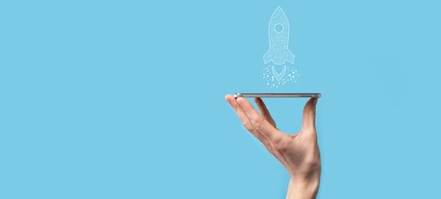 Męskiej Ręki Trzymającej Ikonę Cyfrowy Przezroczysta Rakieta. Koncepcja Biznesowa Uruchamiania. Rakieta Startuje I Wzbija Się W Powietrze. Koncepcja Pomysłu Na Biznes. Premium Zdjęcia