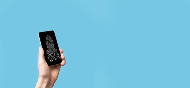 Męskiej ręki trzymającej ikonę cyfrowy przezroczysta rakieta. koncepcja biznesowa uruchamiania. rakieta startuje i wzbija się w powietrze. koncepcja pomysłu na biznes.