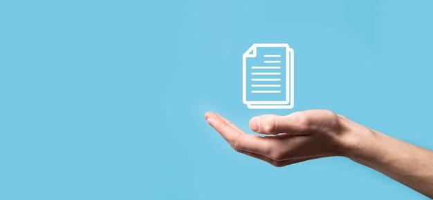 Męskiej ręki trzymającej ikonę dokumentu na niebieskim tle. system danych zarządzania dokumentami biznes koncepcja technologii internetu. firmowy system zarządzania danymi dms.