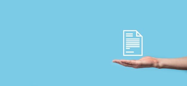 Męskiej ręki trzymającej ikonę dokumentu na niebieskim tle.