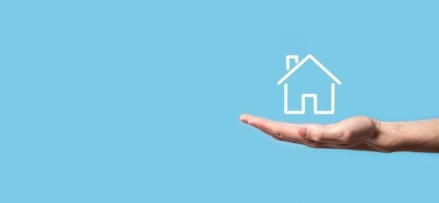 Męskiej ręki trzymającej ikonę domu na niebieskim tle. ubezpieczenie mienia i koncepcja bezpieczeństwa. koncepcja nieruchomości. baner z miejsca na kopię.