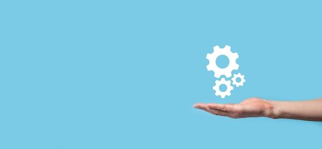 Męskiej ręki trzymającej ikonę koła zębate, ikona mechanizmu na wirtualnych ekranach na niebieskim tle. system automatyzacji procesu technologicznego koncepcja biznesowa. transparent.
