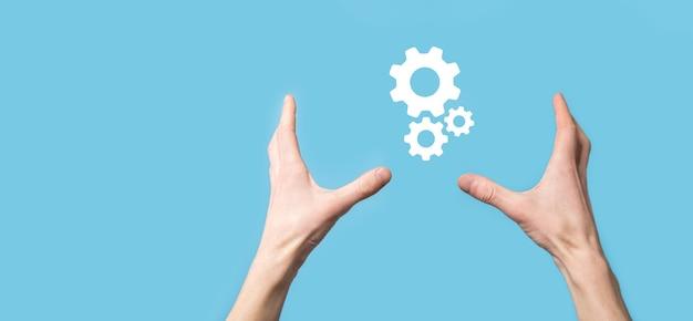 Męskiej ręki trzymającej ikonę koła zębate, ikona mechanizmu na wirtualnych ekranach na niebieskim tle.