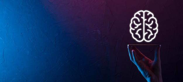 Męskiej ręki trzymającej ikonę mózgu na neonowym tle czerwony, niebieski. sztuczna inteligencja machine learning business internet technology concept. baner z miejscem na kopię