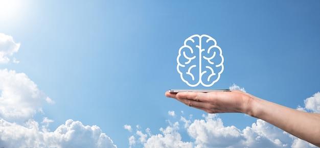 Męskiej ręki trzymającej ikonę mózgu na niebieskiej powierzchni