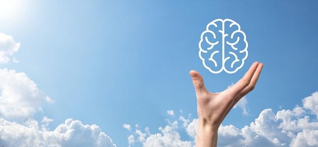 Męskiej ręki trzymającej ikonę mózgu na niebieskim tle. sztuczna inteligencja machine learning business internet technology concept.banner z miejsca na kopię.